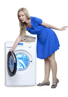 Happy housewife woman in a dress leans over and opens the door of a new washing machine