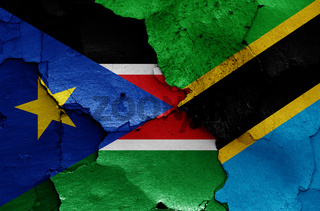 flags of South Sudan and Tanzania painted on cracked wall