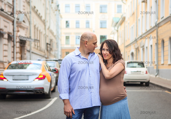 Loving pregnant couple on city street