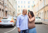 Loving pregnant couple on city street