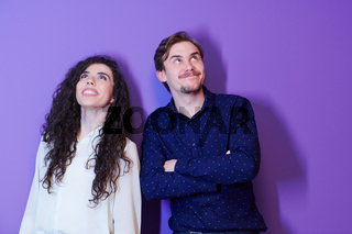 portrait of young couple isolated over purple background