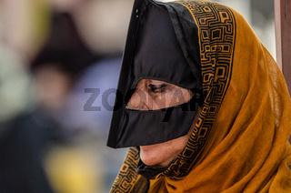 An Omani Bedouin woman wearing a traditional Batoola face covering, Nizwa Souk, Oman