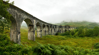High resolution panorama of Glenfinnan railway viaduct (location from Harry Potter movie) shot from side, on overcast day with grey sky and lot of green grass and trees around. Inverness, Scotland