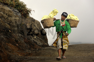 workers carry basket full of sulfur on their shoulder and unload the baskets 3,5 Km away.Indonesia