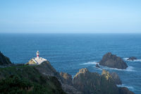 the Cabo Ortegal lighthouse in Galicia with green cliffs and sunlight and deep blue ocean