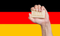 Caucasian male hand holding soap with words: Bitte Hande Waschen against a German flag background