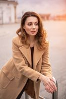 Beautiful Parisian woman standing outdoors posing leaned on handrail for camera in an autumn beige coat, beautiful hair with urban city background. Vertical portrait. Warm tinted photo