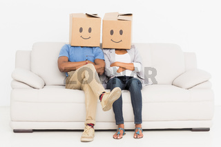 Young couple with happy smiley boxes over faces