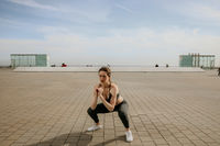 Woman with perfect body doing squats outdoor. Horizontal.