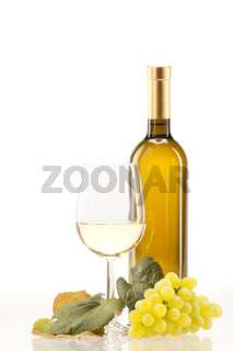 White wine in glass with grapes against a white background
