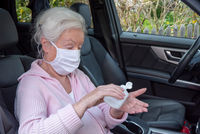 Senior woman with face mask disinfects her hands in the car