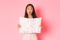 Travelling, lifestyle and tourism concept. Amused beautiful asian girl on vacation, tourist looking at map and making wondered, excited expression, explore city sightseeings, pink background