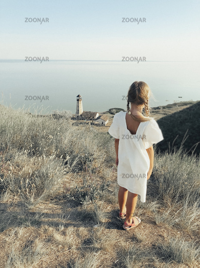 Little girl standing on hill against sea