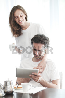 Couple using tablet during breakfast