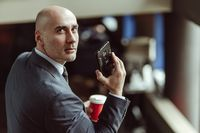 Bald businessman looking at camera turned from back. Caucasian man wearing a business suit, glasses and tie talking on cell phone while getting down on escalator or stairs
