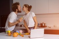 Beautiful young couple kissing feeding each other making fun at modern kitchen and smiling while cooking at home. Pretty girl feeds or nursing her boyfriend