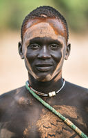 MUNDARI TRIBE, SOUTH SUDAN - MARCH 11, 2020: Young man with ash painted ornament on face smiling and looking at camera in Mundari Tribe village in South Sudan, Africa