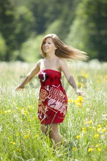 Tanzendes Maedchen in einer Blumenwiese