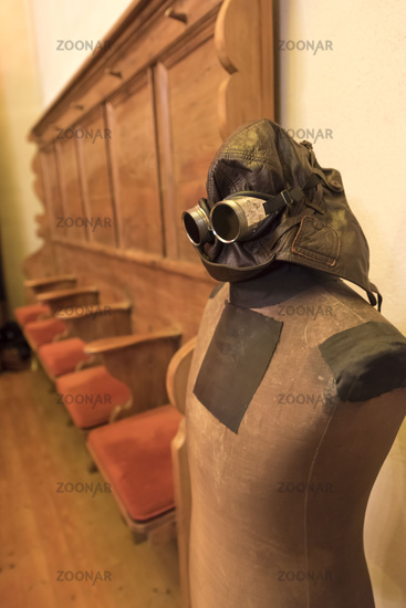 Old tailor doll with leather helmet and glasses stands in front of empty pews