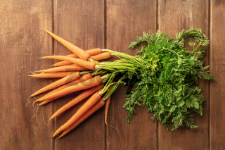 Fresh organic raw carrots on a dark rustic wooden background, shot form the top