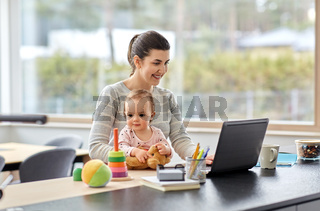 mother with baby and laptop working at home office