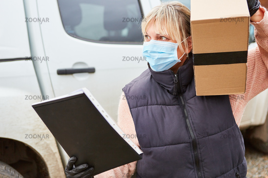 Lieferdienst Paketbotin mit Mundschutz liefert Paket aus