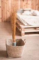 Natural home decor in wooden interior of bedroom. Bouquet of dried sticks in vase and wicker basket at floor