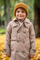 A cute little boy in an autumn coat and a hat is standing on the autumn street and smiling cutely at the camera. Tinted image