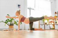 happy pregnant woman doing yoga table pose at home