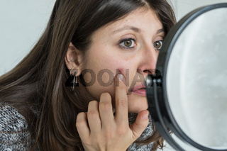 Young woman looks worried in the mirror at the pimple on her face