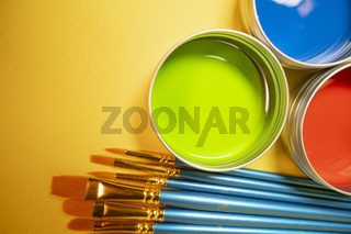 Red Green and Blue Paint Cans on Purple Background With Brushes