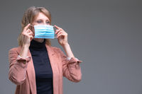Blond woman hold her surgical mask