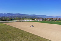 Lonely tractor at sowing work in a field, Chavanne-de-Bois, Canton of Geneva, Switzerland