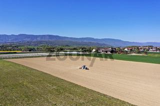 Traktor bei Feldarbeiten zur Aussaat auf einem Feld, Kanton Genf, Schweiz