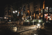Night scene of an elegant outdoor bar illuminated by small lamps among the trees and plants