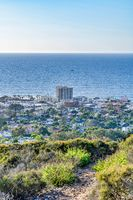 Mountain hiking trail overlooking ocean and building in San Diego California