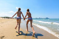 Two girls run along the a beach