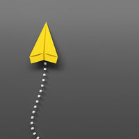 yellow paper plane on a gray background