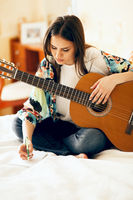 Woman writing song on bed