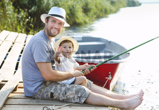 Father with little son fishing on the shore of the river
