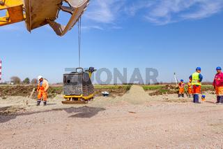 Vibration plate machine hang on excavator's front bucket