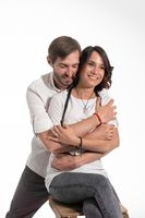 Man hugs woman from behind. Woman sits on chair and smiles. Isolated white background. Presentation of Nanlite Studio LED Lighting. Backstage. June 2020, Kyiv Ukraine. High quality photo