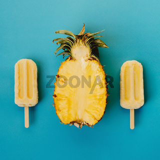 Tropical flat lay of three vegan popsicle and half of ripe pineapple on cyan background