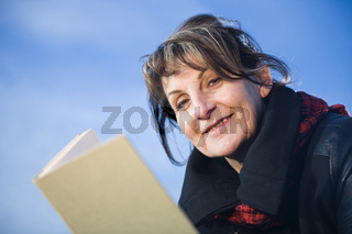 woman with book look into the camera