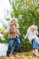 Zwei Mädchen tanzen im Herbst