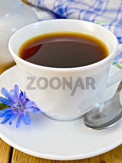 Chicory drink in white cup with milkman and flower on board