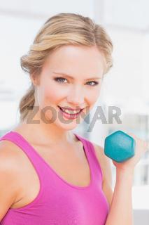 Cute blonde lifting dumbbells and smiling at camera