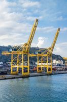 Barcelona, Spain - August 15, 2013: Blue and red metal cargo containers. huge port crane at the Sea Port.