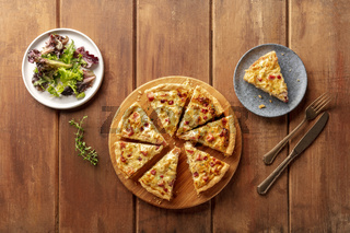 A photo of a quiche with mesclun salad leaves, shot from the top on a dark rustic wooden background