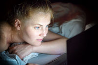 Young woman lying in bed with laptop